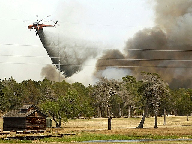 Firefighting helicopters dump water and flame retardant after loading up with water from a pond at Lost Pines Golf Club as they fight a fire in Bastrop State Park September 6, 2011 in Bastrop, Texas. Several large wildfires have been devastating Bastrop County for the last two days.