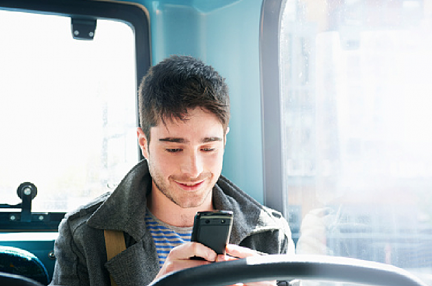 man texting on a bus