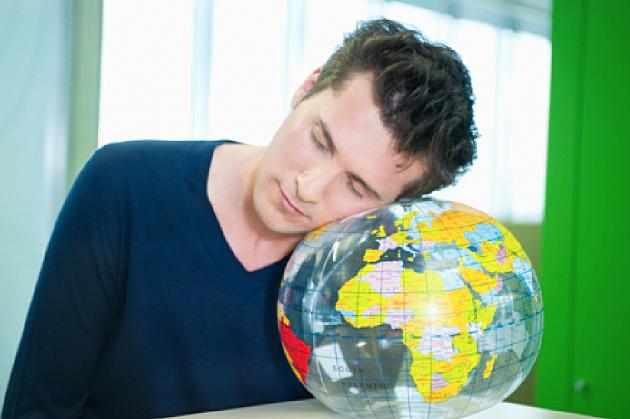 Lazy man sleeping on a globe