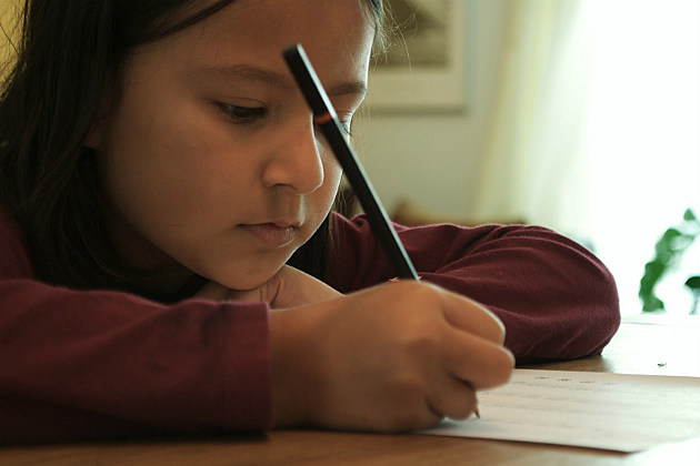 a little girl struggles with her homework