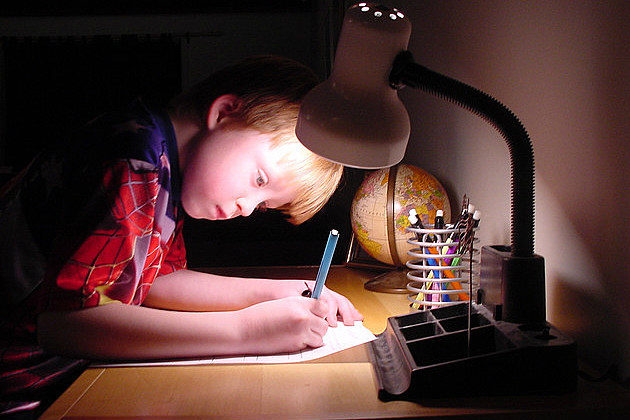 a little boy does homework without distractions