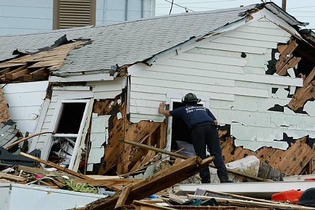 A rescue worker searches damaged homes after Hurricane Ike.