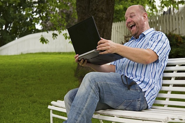 Happy Man in a Park with Laptop
