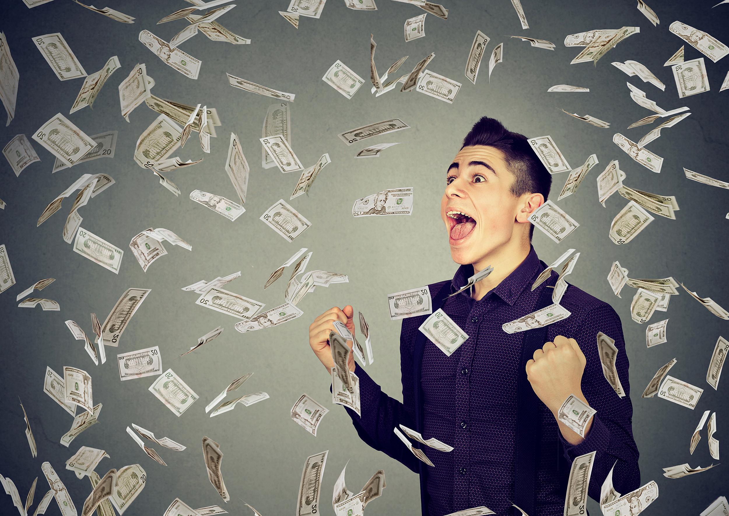 Man celebrates success under money rain falling down dollar banknotes